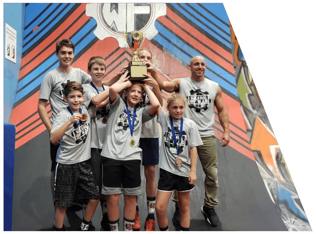 A group of kids posing with medals at The Warrior Factory Summer Camp